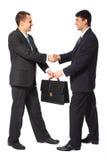 Ein Geschäftsmann gibt einem anderen Aktenkoffer volle Karosserie Lizenzfreies Stockbild