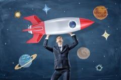 Ein Geschäftsmann hält ein Modell von einem Retro- geschaukelt über seine nahen Hauptzeichnungen von Planeten und von Sternen stockfoto