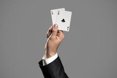 Ein Geschäftsmann Holding An Aces auf Gray Background Stockfotografie