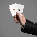 Ein Geschäftsmann Holding An Aces auf Gray Background Stockfoto