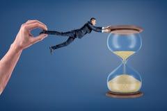 Ein Geschäftsmann kann auf große sandglass halten, weil keine riesige Hand ihn weg schleppt stockfoto