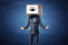 Ein Geschäftsmann mit bewaffnet vor ihm Palmen oben und ein Kopf ersetzt durch einen Fernsehkasten durch ein Auge auf dem Schirm Lizenzfreies Stockbild