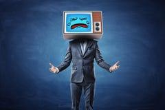 Ein Geschäftsmann mit den Händen drehte sich vor ihm mit Palmen hoch und ein Fernsehen tragend mit einem traurigen schreienden Ge Lizenzfreie Stockfotos