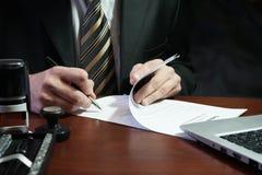 Ein Geschäftsmann setzt seine Unterschrift auf den Vertrag Stockfotografie