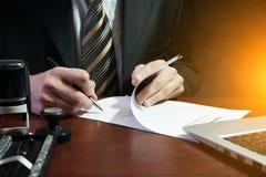 Ein Geschäftsmann setzt seine Unterschrift auf den Vertrag Lizenzfreies Stockbild