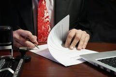 Ein Geschäftsmann setzt seine Unterschrift auf den Vertrag Stockbilder