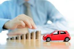 Ein Geschäftsmann ein Spielzeugauto und ein Stapel Münzen Lizenzfreie Stockfotos