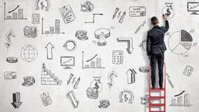 Ein Geschäftsmann steht auf einer roten Leiter und zeichnet Finanzillustrationen auf einer Weilewand lizenzfreies stockbild
