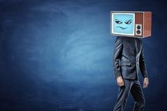 Ein Geschäftsmann steht halb-gedreht und bereitet vor, um beim Tragen eines alten Fernsehens mit einem skeptischen Emoticon auf s Lizenzfreies Stockfoto