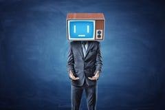 Ein Geschäftsmann steht mit seinen Hände gedrehten Palmen oben vor ihm und trägt einen traurigen Fernsehschirm auf seinem Kopf Stockfoto