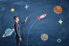 Ein Geschäftsmann steht nahe einer Tafel mit Zeichnungen von Planeten und von Punkten zur Rakete lizenzfreie stockbilder