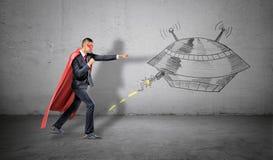 Ein Geschäftsmann in werfenden Durchschlägen eines roten Superheldkaps an einer Wandzeichnung eines UFO, das an ihm schlägt Lizenzfreie Stockfotografie