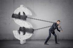 Ein Geschäftsmann zerrt an einer Kette, die versucht, ein großes konkretes Dollarzeichen von seinem Platz zu bewegen stockbild