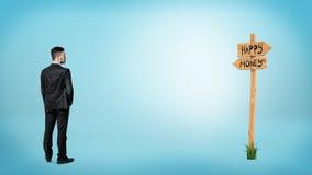Ein Geschäftsmann zurück gedreht und einen Wegweiser betrachtend mit Richtungsschreiben ` Geld ` und ` glücklichem ` Stockfotografie