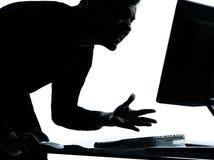 Ein Geschäftsmannschattenbild, das Computerverärgertes missfallen berechnet Lizenzfreie Stockfotos