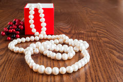 Ein Geschenk in einem roten Kasten und in den Perlen bördelt auf einem hölzernen Hintergrund Lizenzfreie Stockfotos