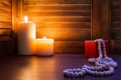 Ein Geschenk in einem roten Kasten und in den Perlen bördelt auf einem hölzernen Hintergrund Stockbild