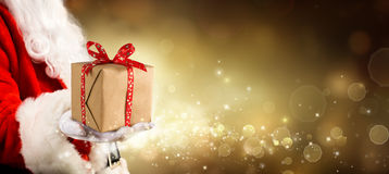Ein Geschenk für Weihnachten - Weinlese-goldener Hintergrund mit Santa Claus Stockbild