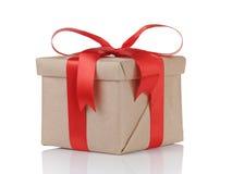 Ein Geschenkweihnachtskasten eingewickelt mit Kraftpapier und rotem Bogen Stockbild