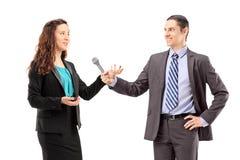 Ein Geschäftsfrau- und Mannesreporter, der ein Interview hat Stockfoto