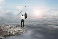 Ein Geschäftsmann, der auf wellenartig bewegender Flagge der Klippe mit Sonnenlicht zujubelt, bewölkt sich Lizenzfreie Stockfotos