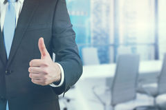 Ein Geschäftsmann, der einen Daumen herauf das Zeichen steht im Büro zeigt Panoramische Singapur-Ansicht Lizenzfreies Stockbild