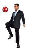 Ein Geschäftsmann, der jonglierende Fußballkugel spielt Lizenzfreie Stockfotos