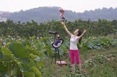 Ein geschickter weiblicher Fotograf mit ihrem Lappenbaby Lizenzfreie Stockbilder