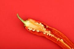 Ein geschnittener Pfeffer des scharfen Paprikas auf rotem Hintergrund Stockfotografie
