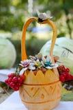 Ein geschnitzter Kürbis Im Korb von Kürbisen sind Blumen und Eberesche stockfotos