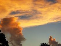 Ein Gesicht in der Wolke, das Sonnenunterganggeben oben betrachtend Daumen stockfotos