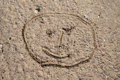 Ein Gesicht skizziert auf dem Sand Children' s-Zeichnung gezeichnet mit einem Stock auf einer bewaldeten Straße stockbilder