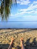 Ein Gesichtspunkt geschossen mit den Beinen und den Füßen einer Mannvertretung, die auf einem schönen sandigen Strand übersieht b stockbilder