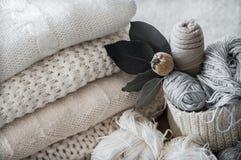 Ein gesponnener Korb mit weißem Thread für das Stricken und die Stricknadeln Weiße Strickjacken und Garn für strickende Nahaufnah lizenzfreies stockbild