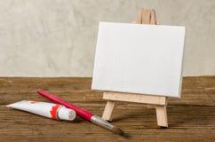 Ein Gestell mit einem leeren Segeltuch, einer Farbe und einer Bürste Lizenzfreie Stockfotos