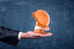 Ein gestreifter Verkehrskegel und ein orange Schutzhelm, die auf Geschäftsmann ` s Palme stehen Stockfoto