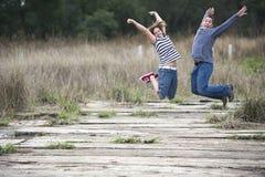 Das glückliche Paar draußen springend Stockbild