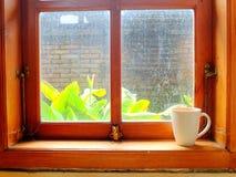 Ein Getränk im Becher im hölzernen Fenster am sonnigen Tag Lizenzfreies Stockfoto