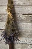 Ein getrocknetes Bündel Lavendel blüht das Hängen oben an einer alten strukturierten hölzernen Wand Stockfoto