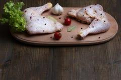 Ein gewürzter roher Hühnerschenkel auf dem Tisch vor der Erbeutung mit Co Stockfotos