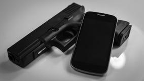 Ein Gewehr und ein modernes intelligentes Telefon, Schwarzweiss lizenzfreies stockbild