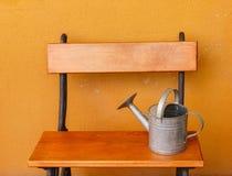 Ein Gießkannealuminium gelegt auf eine Holzbank Lizenzfreies Stockbild