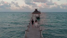 Ein glückliches in den Liebespaaren, die hinunter ein hölzernes Dock außerhalb eines strandnahen Erholungsortes nahe Cancun, Mexi stock footage