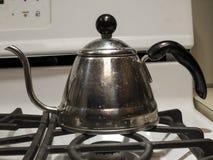 Ein glänzender Teekessel auf einem Ofen Stockbild