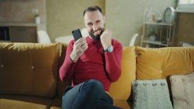 Ein glücklicher bärtiger Mann macht ein erfolgreiches Abkommen oder einen Gewinn mit Telefon und freut sich zu Hause Freiberufler stock video