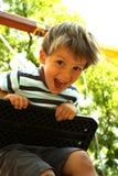Ein glücklicher Junge auf einem Schwingen 4 Stockfotos