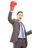 Ein glücklicher junger Geschäftsmann mit roten Boxhandschuhen happi gestikulierend Lizenzfreies Stockfoto