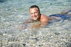 Ein glücklicher lächelnder Mann im Meer Stockbilder