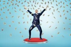 Ein glücklicher und siegreicher Geschäftsmann steht auf einem riesigen roten Knopf unter fallenden vielen 100 Dollarscheine Stockfotos
