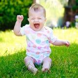 Ein glückliches Baby in einer Weste auf dem Gras im Garten, schreiend Lizenzfreie Stockbilder